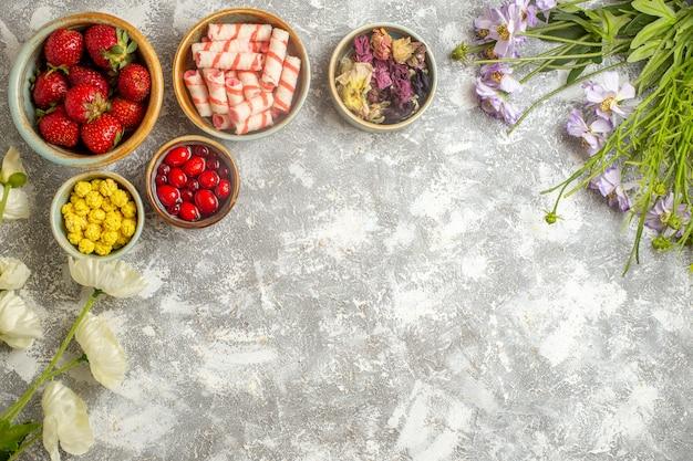 Fragole rosse fresche di vista superiore con le caramelle sulla caramella della frutta della bacca di colore di superficie bianca