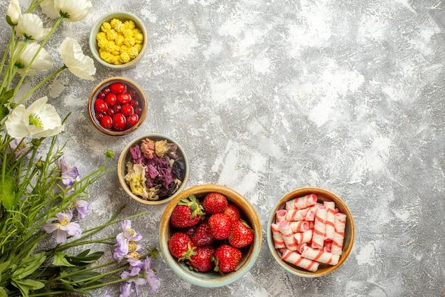 Fragole rosse fresche di vista superiore con le caramelle sulla frutta di bacca fresca della caramella di superficie bianca