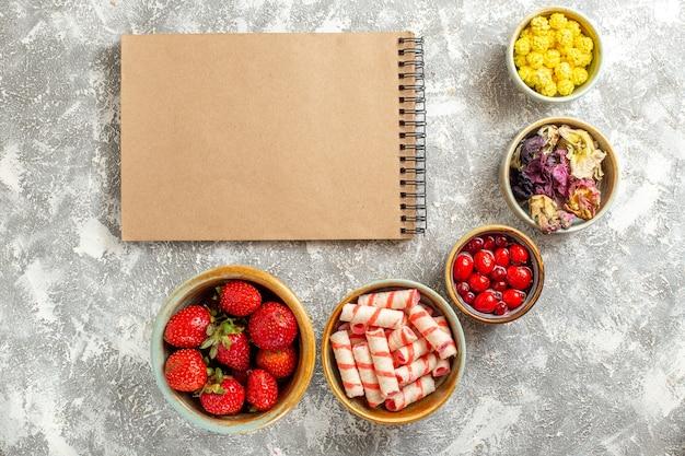 Fragole rosse fresche di vista superiore con le caramelle sul colore della caramella dolce della frutta di superficie bianca