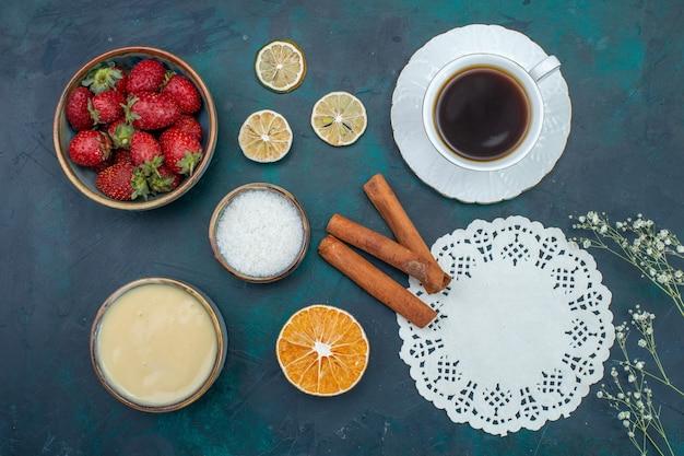 Vista dall'alto di fragole rosse fresche con cannella e tazza di tè sulla superficie blu scuro