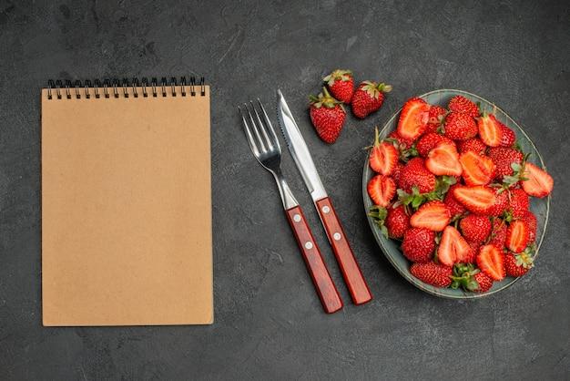 灰色の背景にカトラリーと新鮮な赤いイチゴの上面図