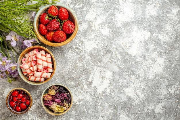 上面図白い表面に花を持つ新鮮な赤いイチゴベリーフルーツ赤いキャンディー