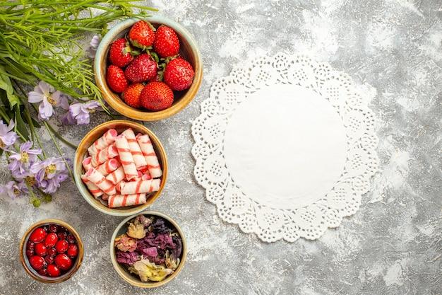 Fragole rosse fresche di vista superiore con i fiori sulla caramella rossa della frutta di bacca di superficie bianca