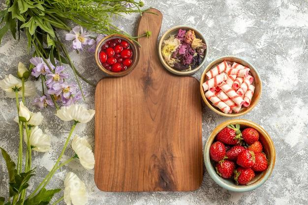 Fragole rosse fresche di vista superiore con i fiori sulla caramella rossa di frutti di bosco di superficie bianca