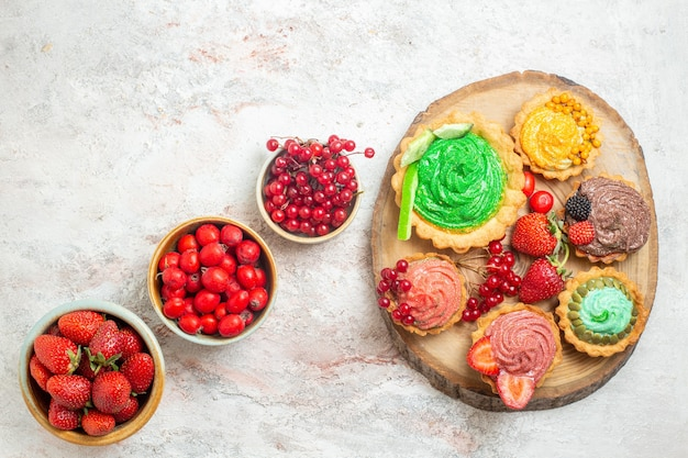 Vista dall'alto fragole rosse fresche con frutta e torte sulla bacca di frutta tavolo bianco