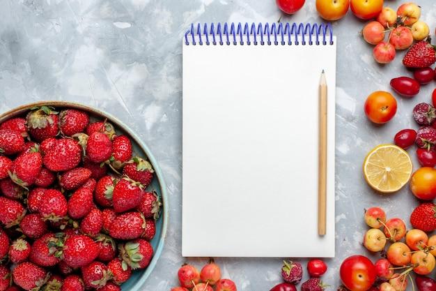 Fragole rosse fresche di vista superiore con altri frutti sulla vitamina fresca della bacca della frutta leggera dello scrittorio