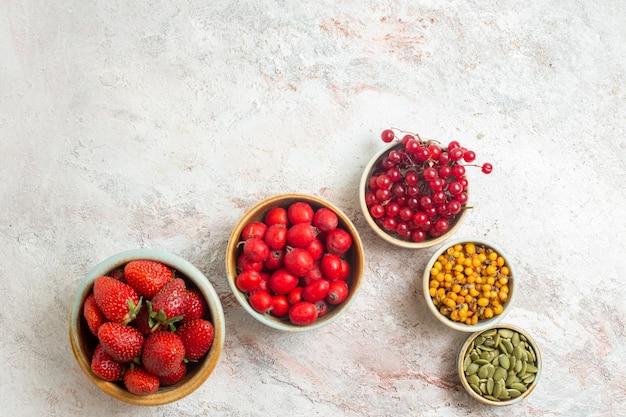Вид сверху свежей красной клубники с другими фруктами на ягодном белом полу