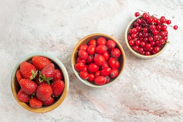 Вид сверху свежей красной клубники с другими фруктами на белом столе, фруктовыми ягодами