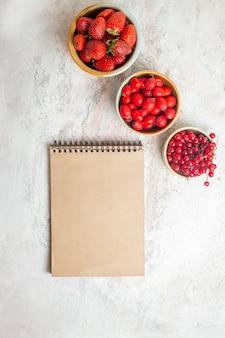 Vista dall'alto fragole rosse fresche con altri frutti sul tavolo bianco, bacche di frutta