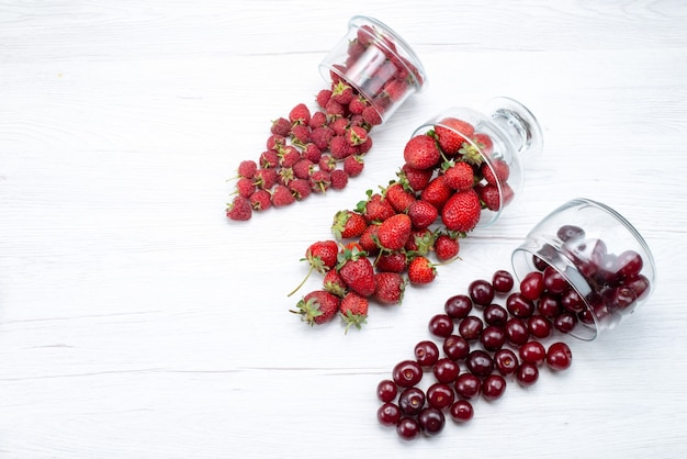 Top view of fresh red strawberries with sour cherries and raspberries on light, fresh fruit berry vitamine
