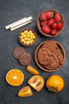 Vista dall'alto fragole rosse fresche con biscotti dolci sul tavolo scuro, biscotto di zucchero fresco