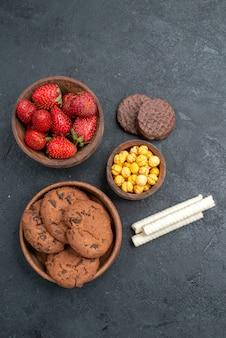 ダークテーブルのシュガークッキーケーキに甘いビスケットと新鮮な赤いイチゴの上面図