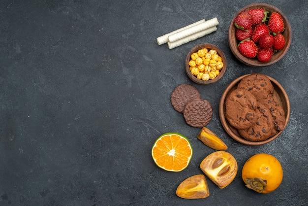 トップビュー暗いテーブルに甘いビスケット、新鮮なシュガークッキーと新鮮な赤いイチゴ
