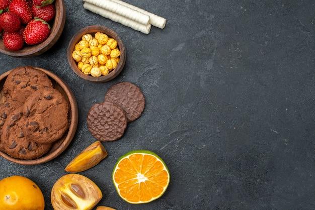 Вид сверху свежей красной клубники со сладким печеньем на темном столе, свежее сахарное печенье