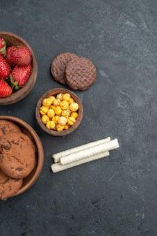 暗いテーブルのシュガークッキーケーキに甘いビスケットと新鮮な赤いイチゴの上面図
