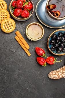 Vista dall'alto fragole rosse fresche con tè e olive su bacca di frutta pavimento scuro fresca