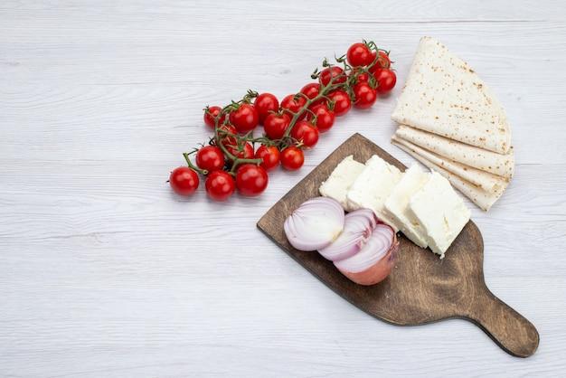トップビュー新鮮な赤いトマトとスライスした白いチーズ玉ねぎとラバッシュは、白い背景の食品食事ランチ写真野菜