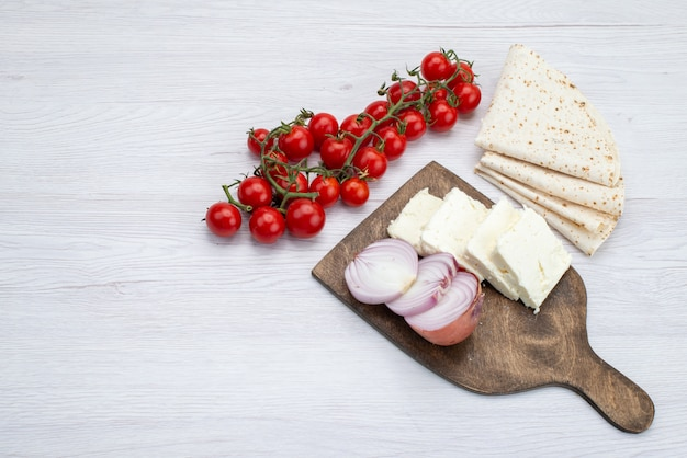 Top view fresh red tomatoes along with sliced white cheese onions and lavash on the white background food meal lunch photo vegetable