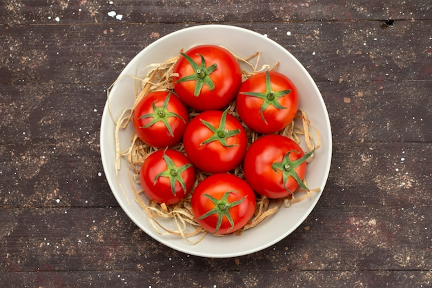 Top view fresh red tomatoes inside white plate on wooden brown