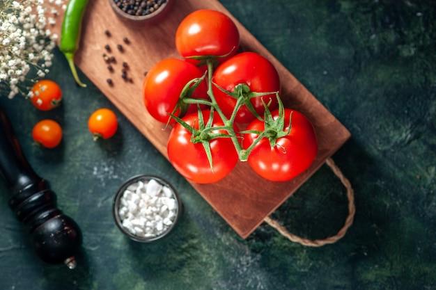 Вид сверху свежие красные помидоры на темной поверхности овощная свежая еда перец цвет спелый салат еда