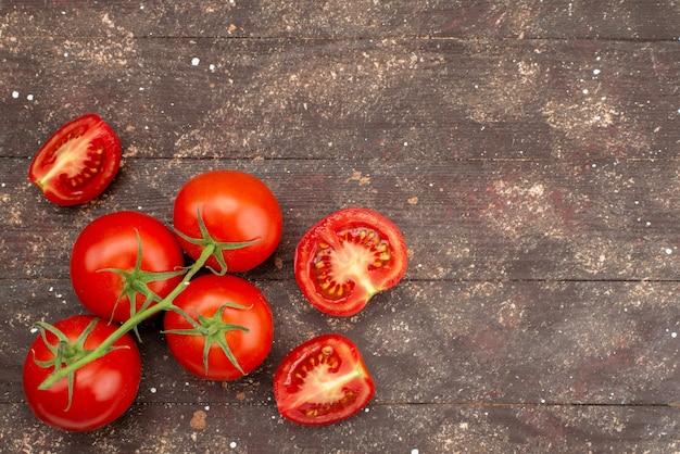 Вид сверху свежие красные помидоры спелые и целые на коричневом