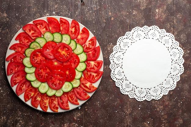 Вид сверху свежих красных помидоров, нарезанных свежим салатом на коричневом пространстве