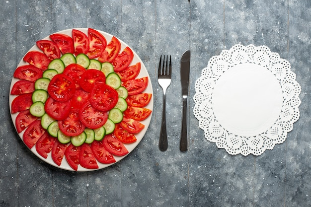 Вид сверху свежих красных помидоров, нарезанных свежим салатом на сером столе