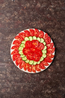 Top view fresh red tomatoes sliced with cucumbers fresh salad on a brown space