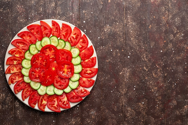 Top view fresh red tomatoes sliced with cucumbers fresh salad on the brown space