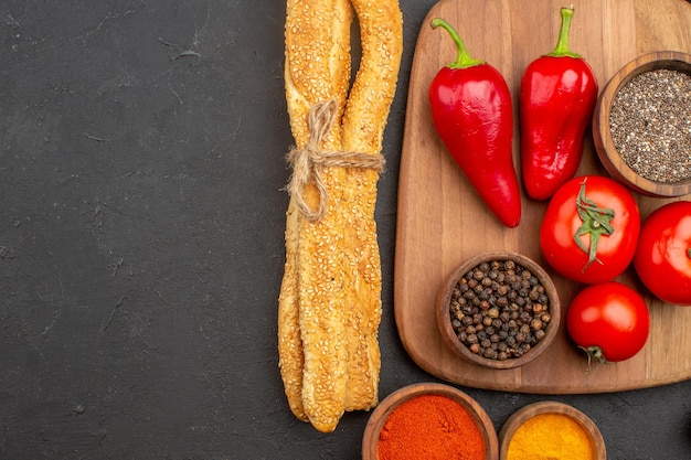 Vista dall'alto di pomodori rossi freschi con pane e condimenti su nero