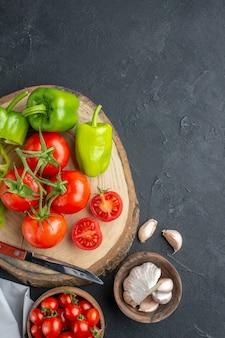 暗い表面にニンニクと緑のピーマンが付いている上面図の新鮮な赤いトマト