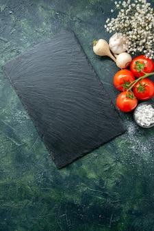 Vista dall'alto pomodori rossi freschi con aglio su sfondo scuro insalata di farina di salute cibo foto a colori