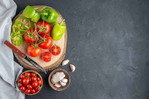Vista dall'alto pomodori rossi freschi con aglio e peperoni verdi su superficie scura