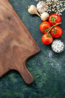 暗い表面の健康食事ダイエットサラダ食品着色料フォトデスクにニンニクと新鮮な赤いトマトの上面図