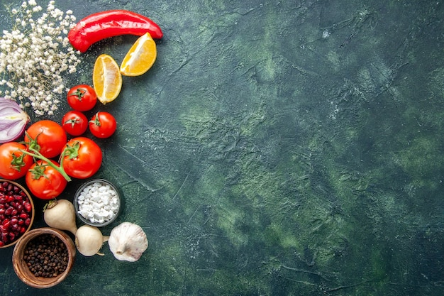 Top view fresh red tomatoes with garlic and seasonings on dark background health meal diet salad food color photo free space