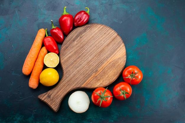 진한 파란색 책상에 레몬 당근과 고추와 신선한 빨간 토마토를 볼 수 있습니다.