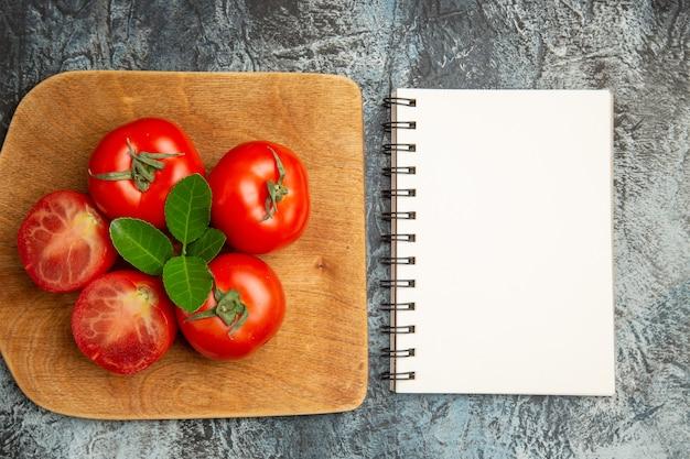 Вид сверху свежие красные помидоры с блокнотом