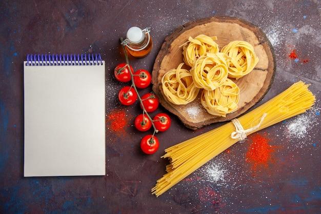 暗い背景に生のイタリアンパスタと生のサラダパスタフードミールの上面図新鮮な赤いトマト