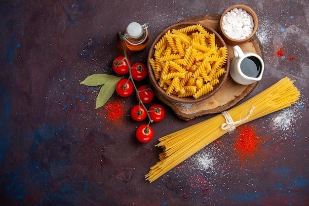 暗い背景の食品生サラダパスタミールに生イタリアンパスタとトップビュー新鮮な赤いトマト