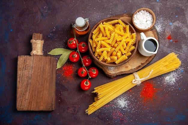 上面図新鮮な赤いトマトと生のイタリアンパスタを暗い表面に添えた生のサラダパスタミール