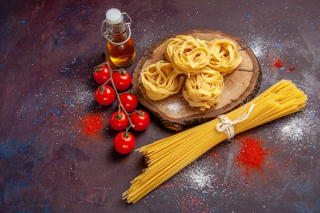 Top view fresh red tomatoes with raw pasta on dark background raw salad pasta food meal