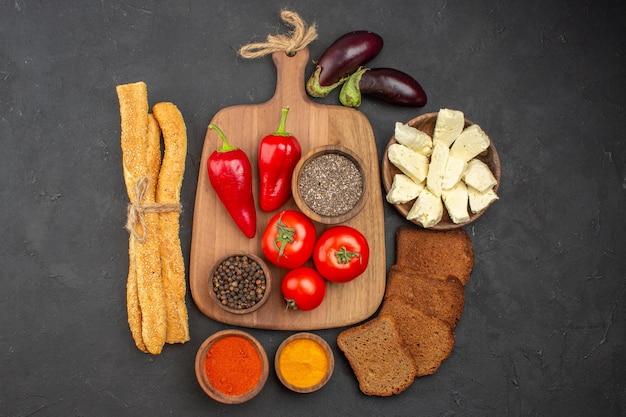 Vista dall'alto di pomodori rossi freschi con condimenti formaggio e pane su nero