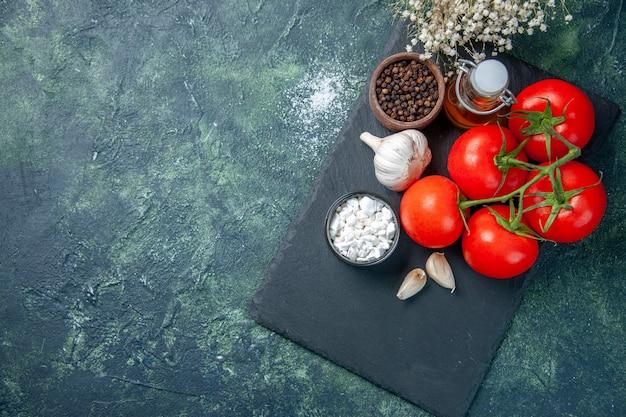 Vista dall'alto pomodori rossi freschi con condimenti su sfondo scuro