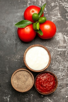 暗い表面に調味料を入れた新鮮な赤いトマトの上面図熟した赤い野菜