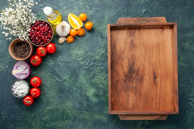 Vista dall'alto pomodori rossi freschi con scrivania in legno su uno sfondo blu scuro salute pasto insalata cibo colore foto dieta spazio libero