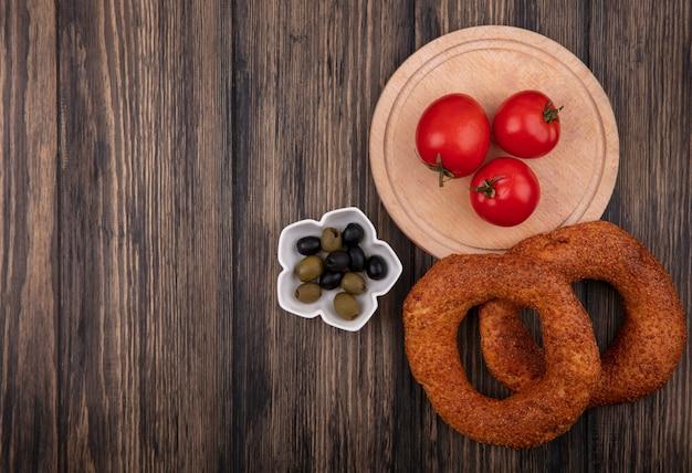 Vista dall'alto di pomodori rossi freschi su una tavola da cucina in legno con olive su una ciotola e bagel isolato su uno sfondo di legno con spazio di copia