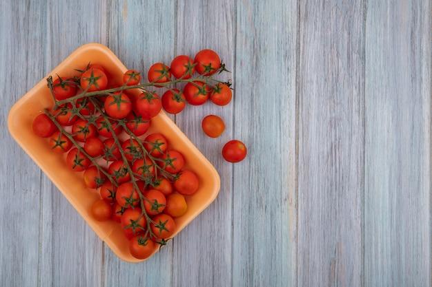 Vista dall'alto di pomodori freschi a grappolo rosso su un contenitore di plastica su un fondo di legno grigio con spazio di copia
