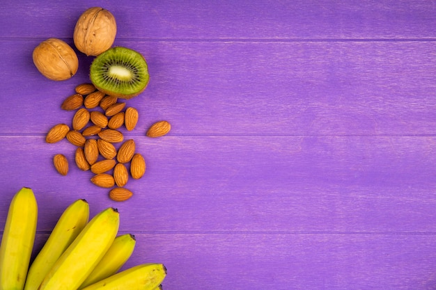 Top view of fresh ripe bananas with almond and kiwi fruits on purple wood with copy space