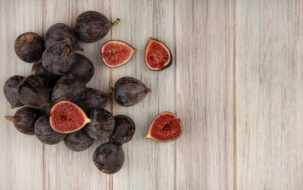 Top view of fresh ripe black mission figs isolated on a grey wooden wall with copy space