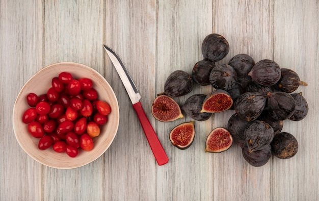 Top view of fresh ripe black mission figs with cornelian cherries on a bowl with knife on a grey wooden wall
